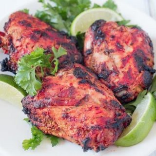 Tandoori Chicken on a white plate with fresh limes wedges and parsley
