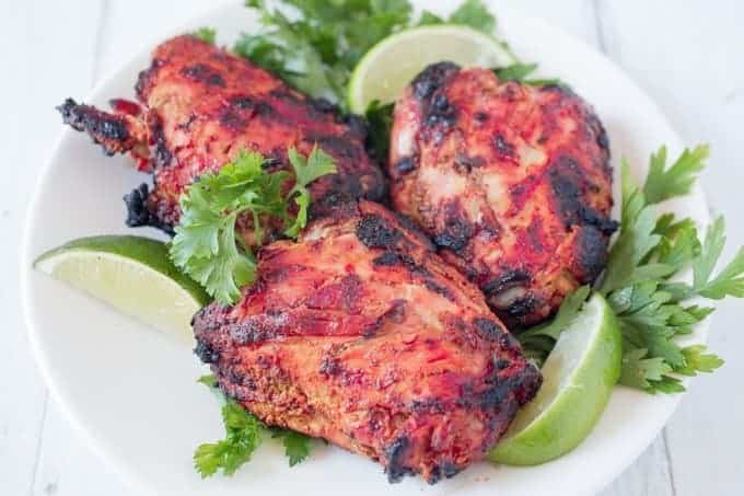 Tandoori Chicken on a white plate with lime wedges and parsley
