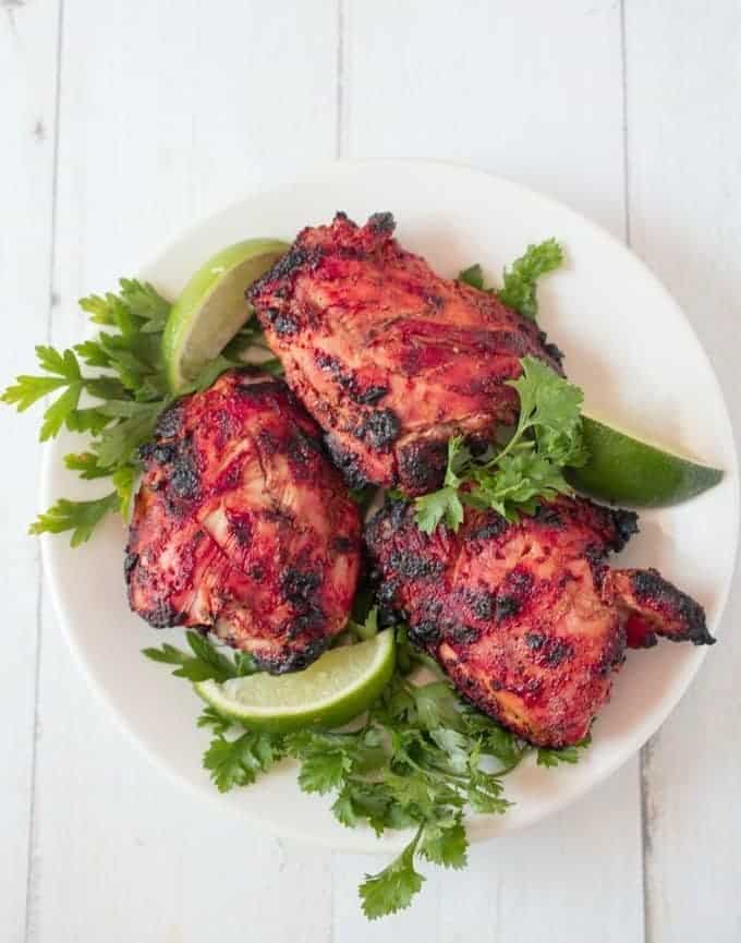 Indian chicken thighs on a platter with parsley and fresh lime wedges