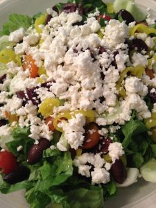 Easy Greek Salad on a plate with a feta cheese on top.