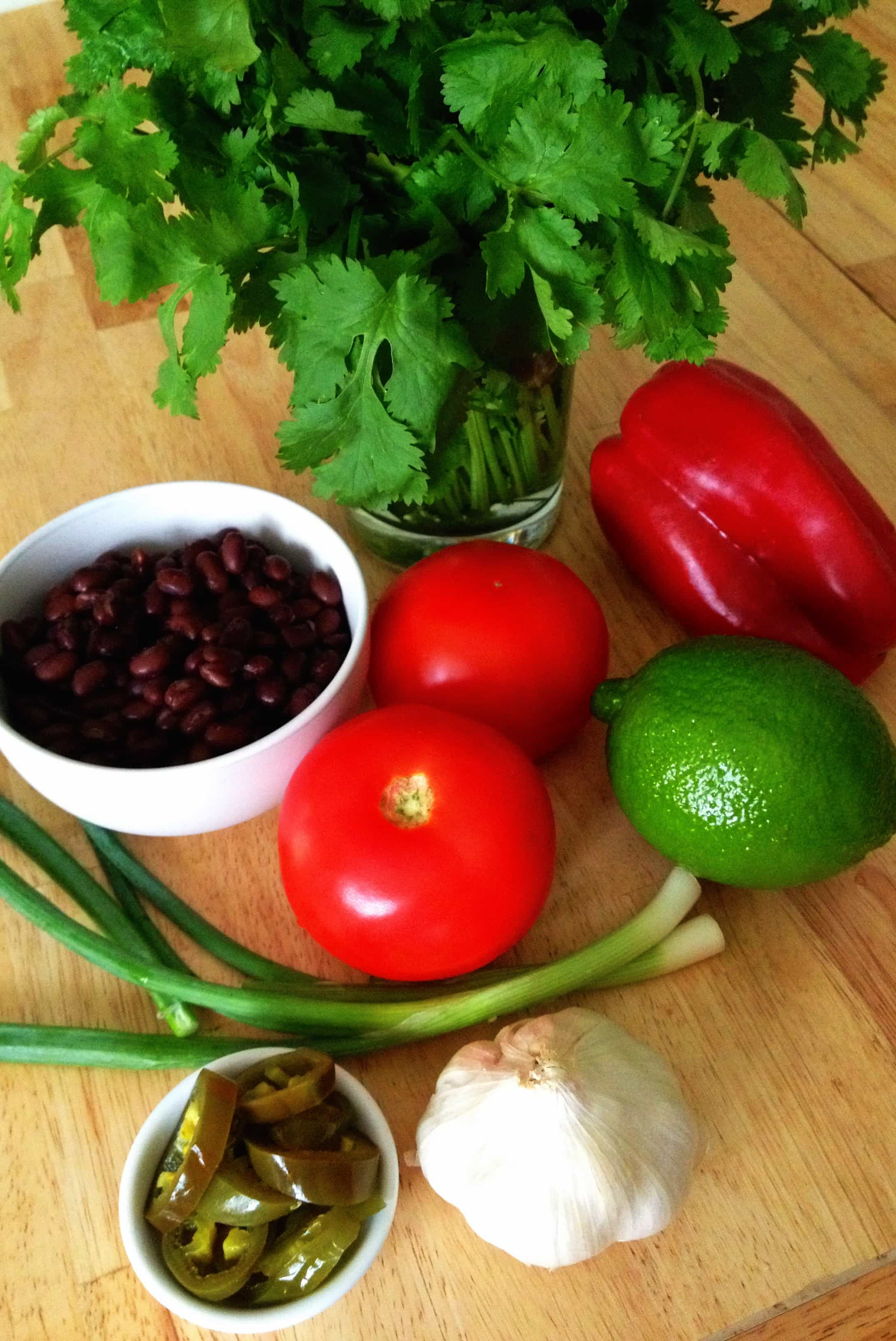 Fresh ingredients (tomatoes, onions, garlic, peppers) for black bean salsa on wooden board