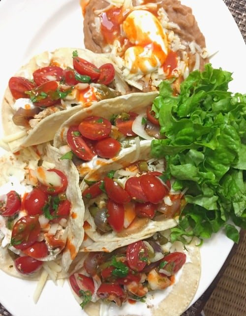Plate of Homemade Tacos with lettuce, pico de gallo, and soft corn tortilla shells.