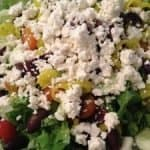 Easy Greek Salad on a plate with feta cheese on top.