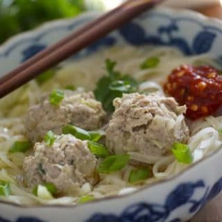 Close up of Asian meatball noodle soup with hot sauce and chopsticks on side of bowl