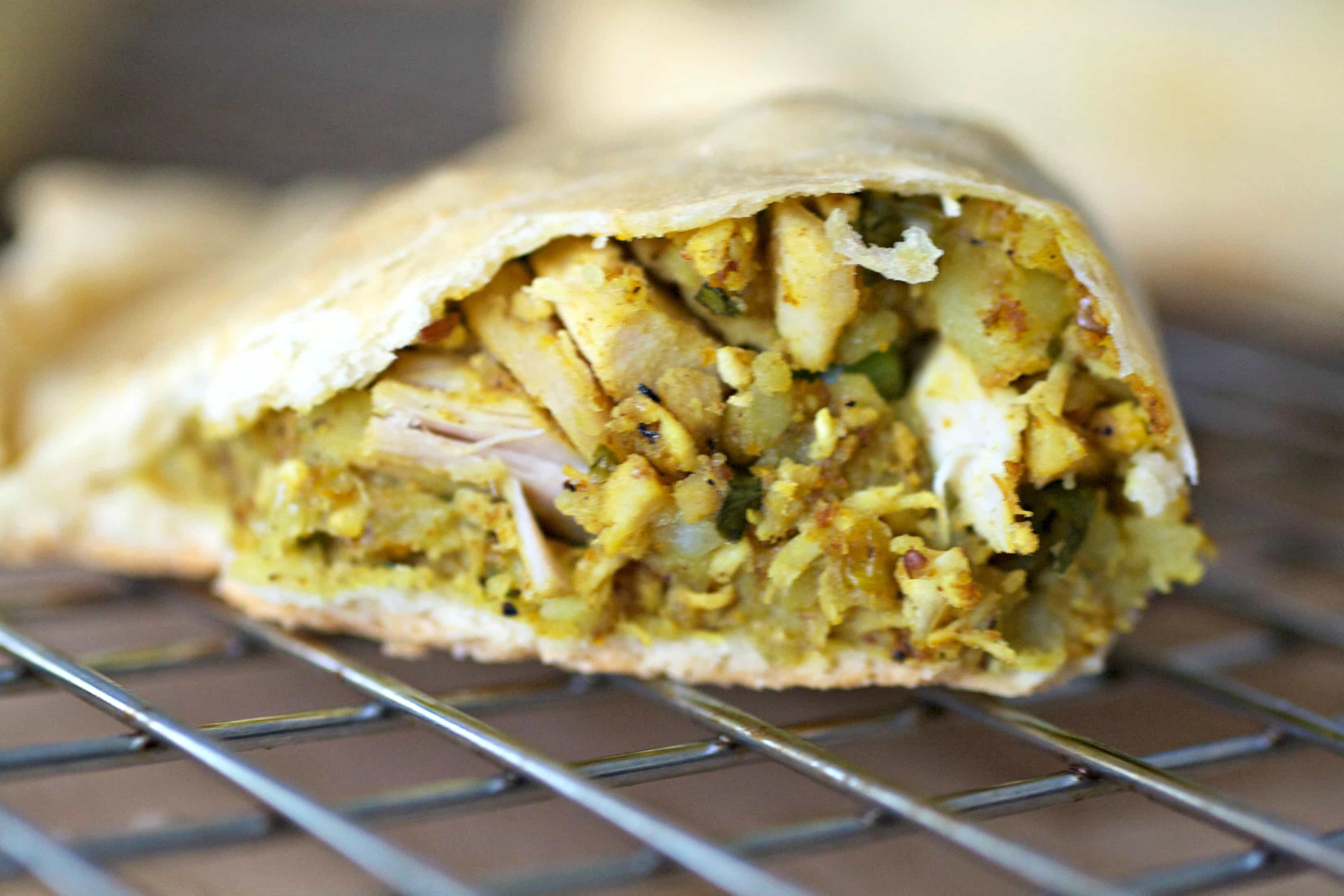 A hand pie cut in half showing the inside with curried turkey filling