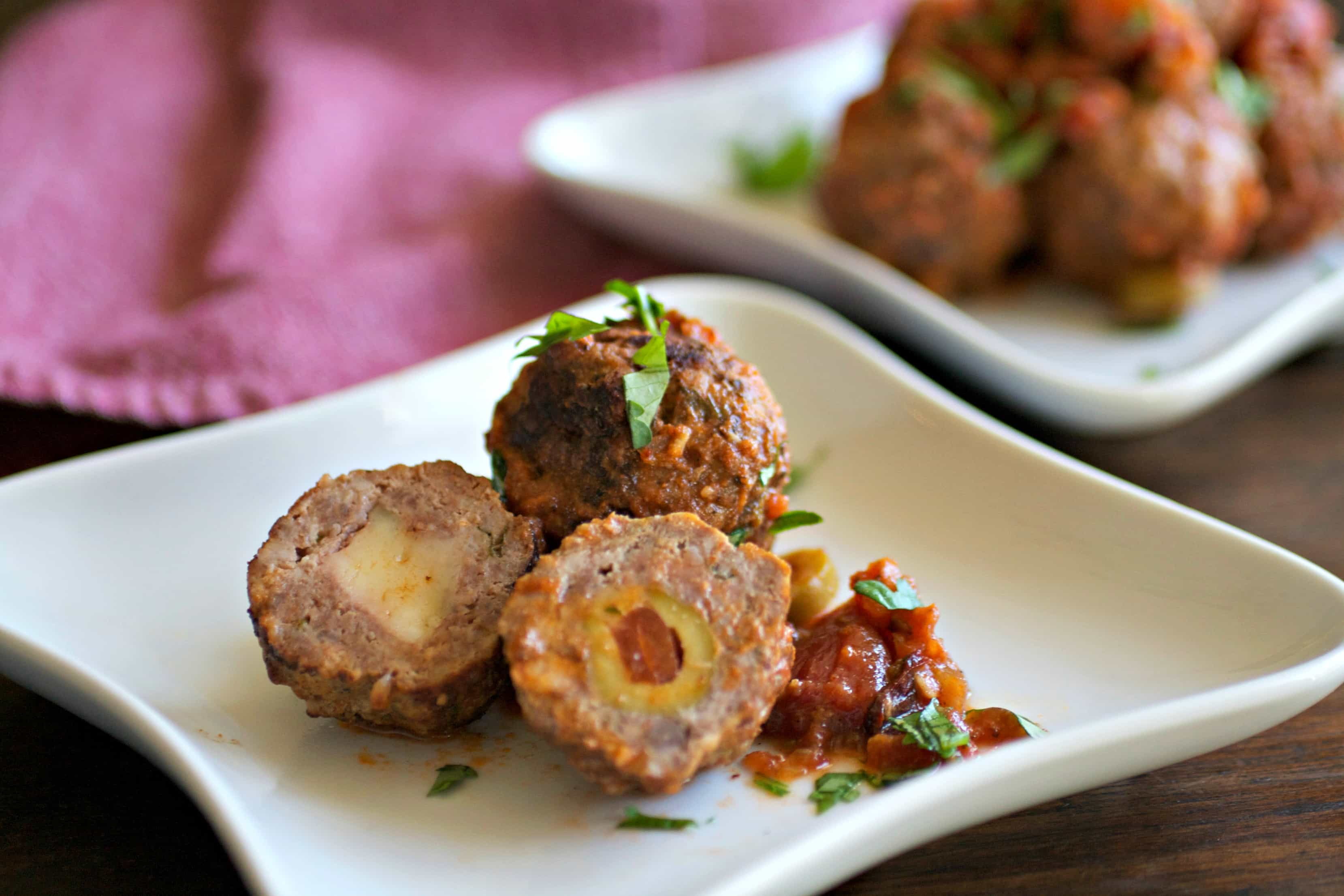 Stuffed meatballs cut in half on a plate
