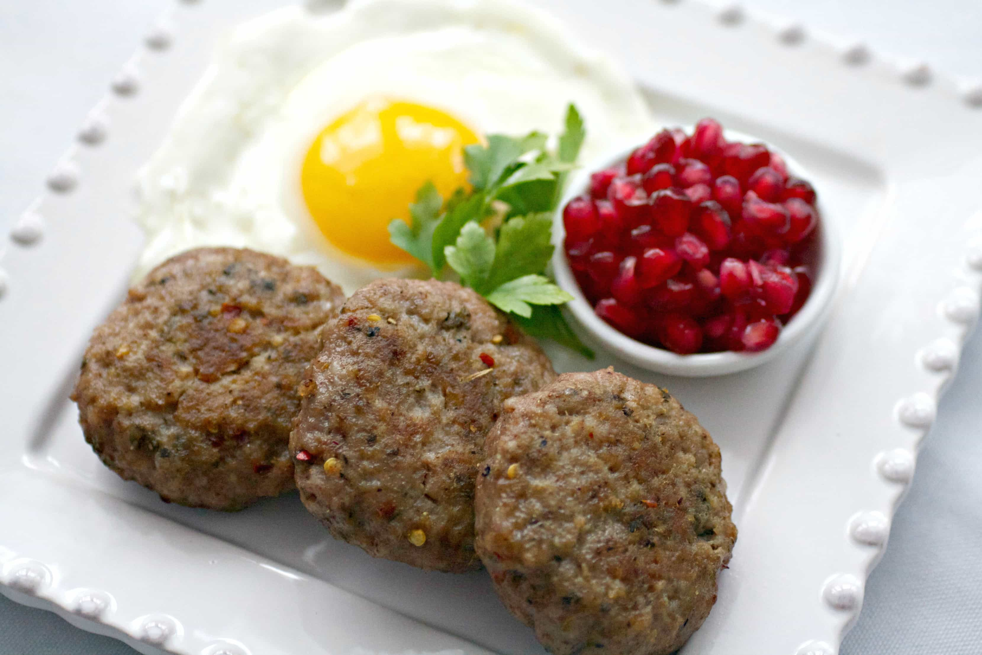 Three cooked breakfast sausage patties on a white square plate with a sunny side up egg and fruit