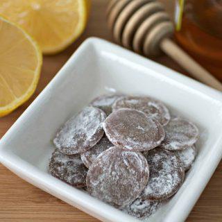 Coated homemade honey lemon ginger cough drops in a bowl