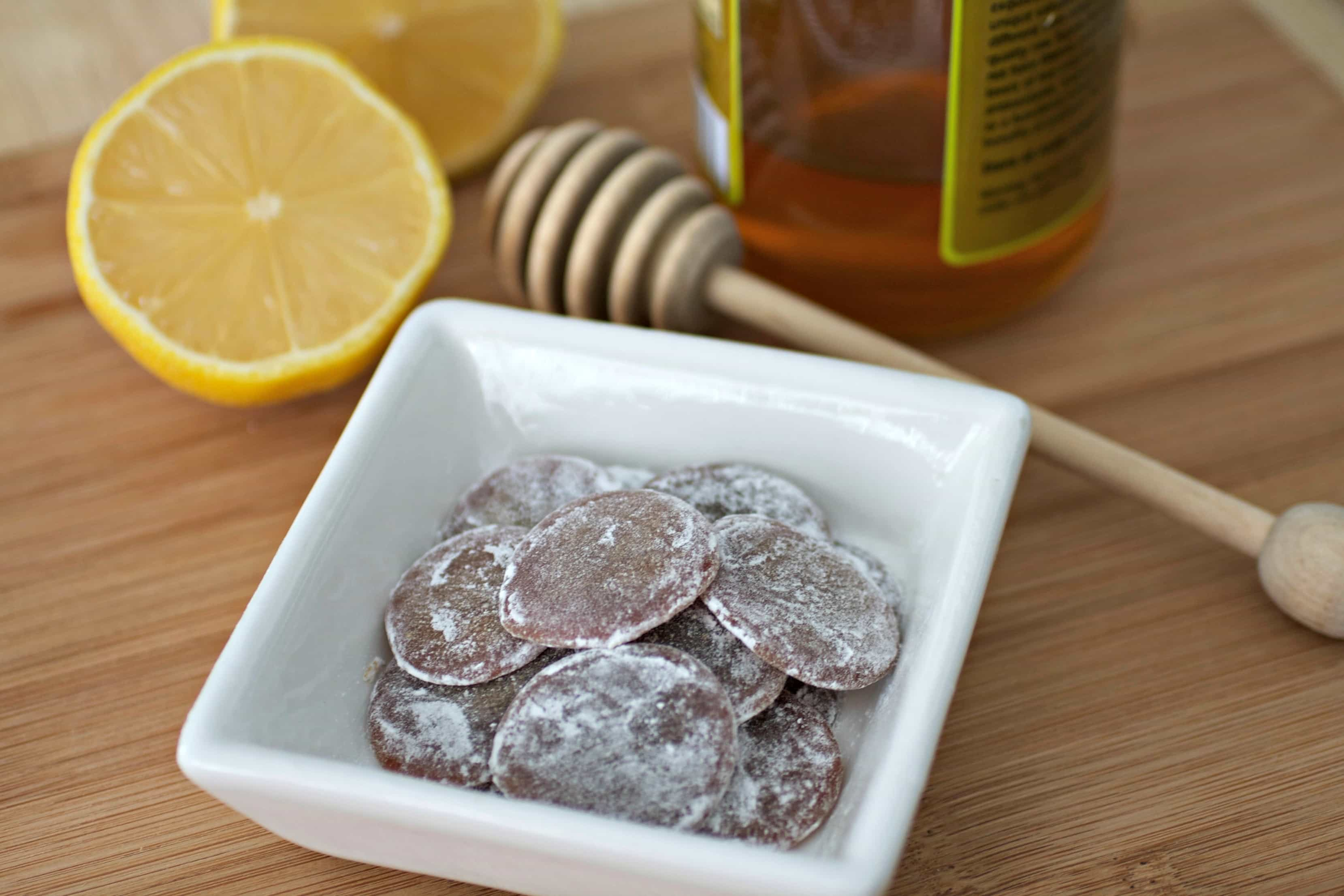 Homemade honey lemon cough drops with jar of honey on side