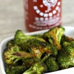 Sriracha roasted broccoli on a white plate with hot sauce in background
