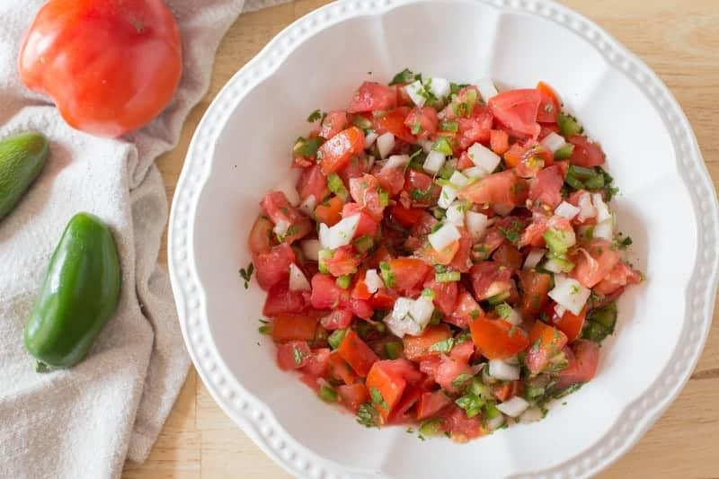 Pico de gallo salsa in a large white serving bowl