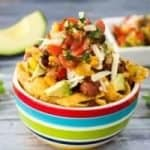 Photo of a vegetarian chili frito pie in a bowl with a pico de gallo salsa