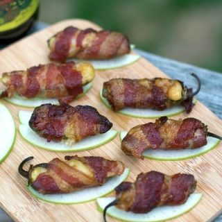 Smoked Jalapeño Poppers on a wooden cutting board on top of an apple slice.