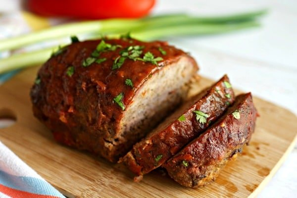 Photo of sliced smoked meatloaf on a wooden cutting board