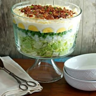 7 Layer Salad in a trifle bowl with white bowls and a large serving spoon