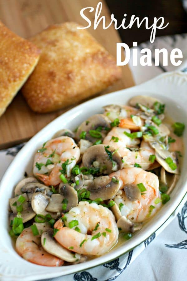 A dish of Shrimp Diane with bread rolls on the side