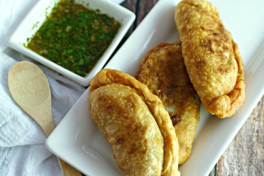 photo of fried cuban beef empanadas with chimichurri sauce on a serving plate