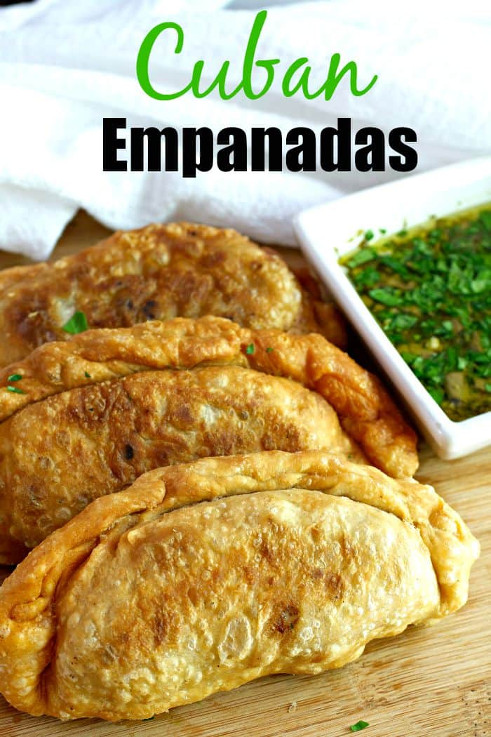 Cuban Beef Empanadas are fried (or baked) hand pies filled with a spiced ground beef mixture with lots of sliced green olives and served with a chimichurri sauce.  Homemade dough recipe is included!