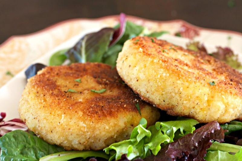 Side of breaded rice cakes on a plate on top of fresh greens