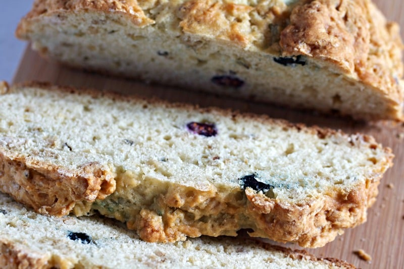 Blueberry Granola Soda Bread slices on top of a wooden cutting board