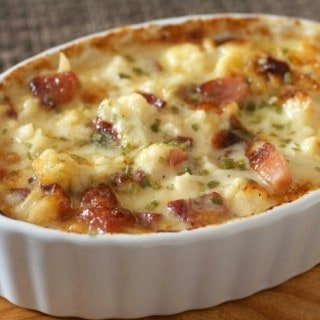 Cheesy Cauliflower with speck ham in a white baking dish on the table.