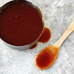 Homemade BBQ Sauce in a pot with a wooden spoon