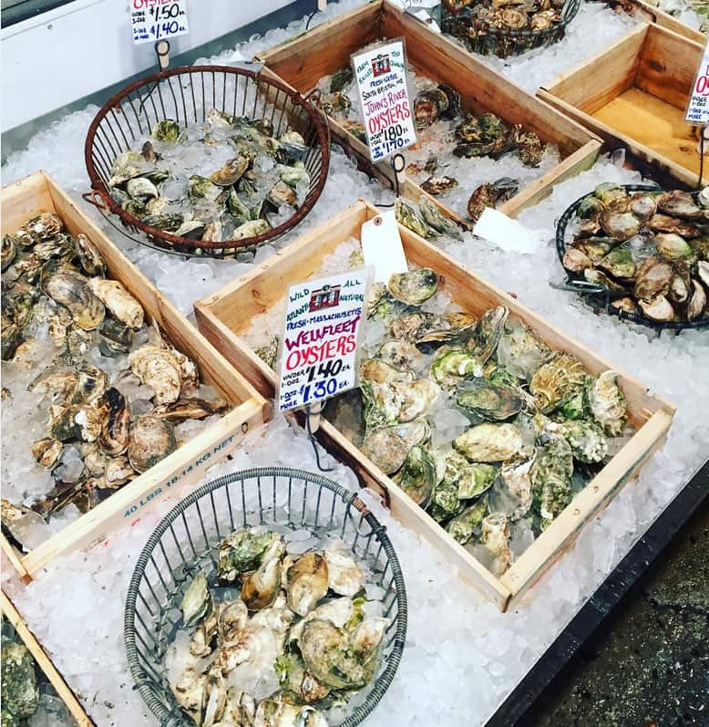 Raw oysters in the shell in baskets and wooden boxes on cushed ice