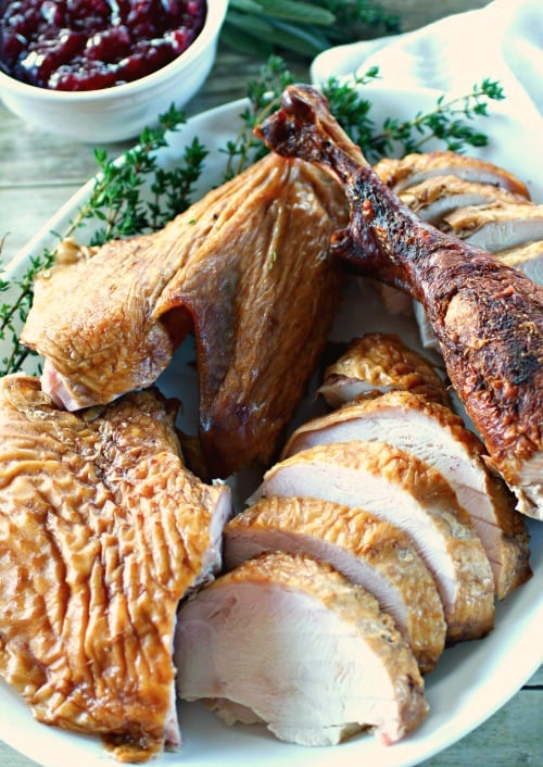 Double Rum Smoked Turkey on a platter with fresh herbs