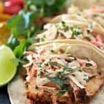 Easy fish tacos lined up on a platter with a fresh lime