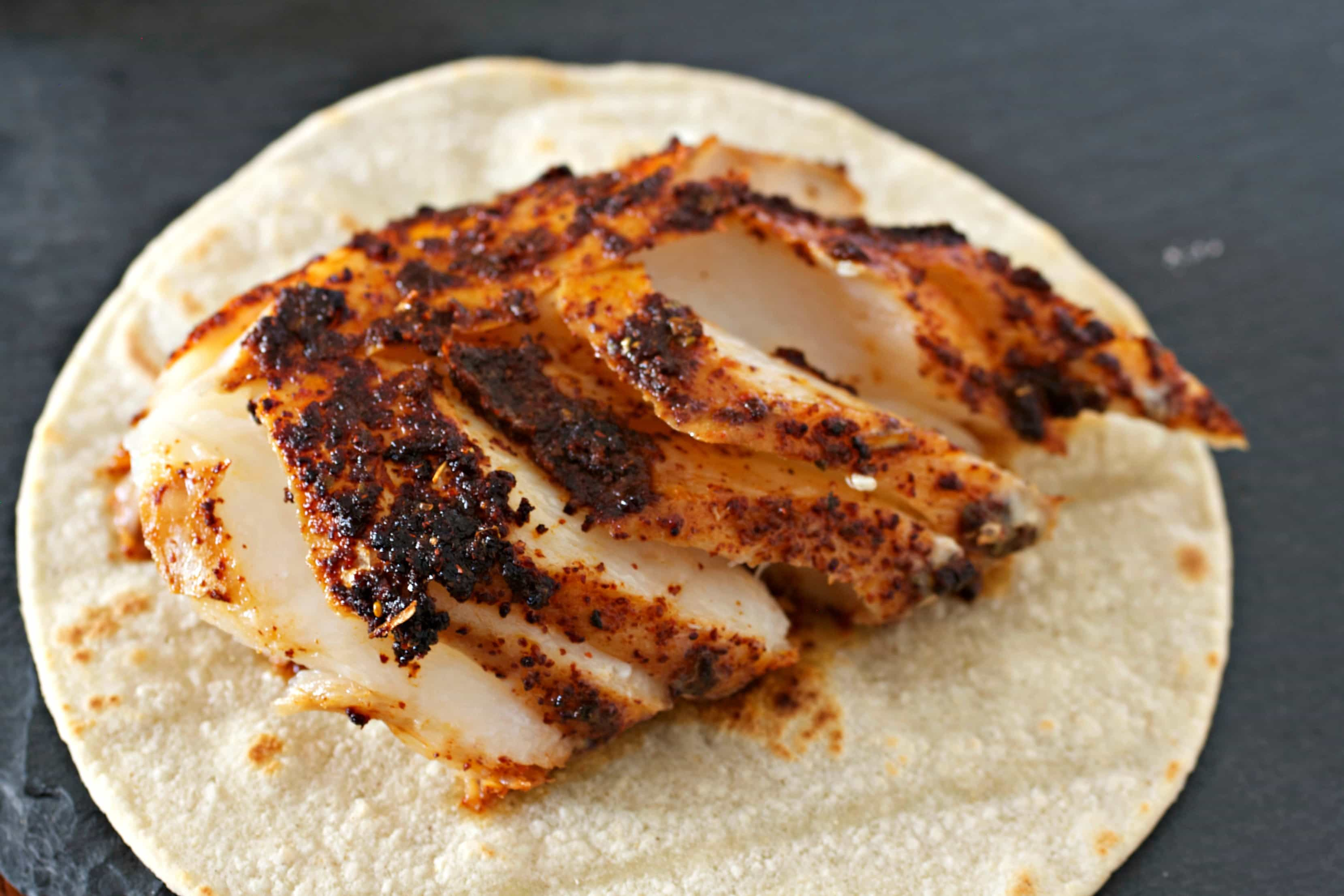 Mexican spiced fish on top of a corn tortilla.