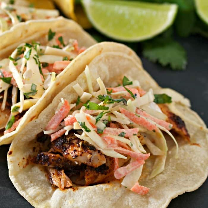 Fresh spicy slaw on top of a grilled fish in a fresh corn tortilla.