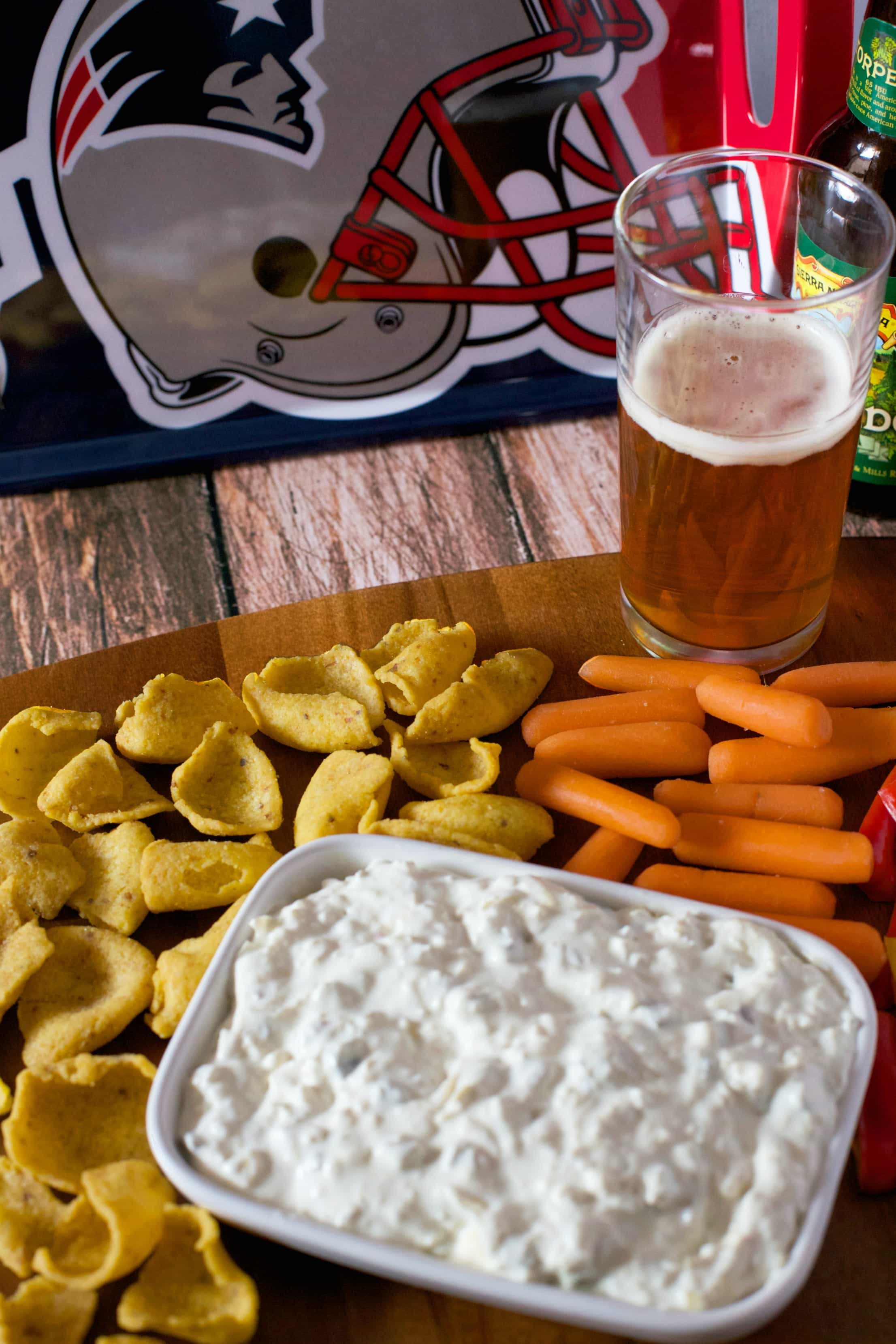 Wooden board with dip appetizer and a beer
