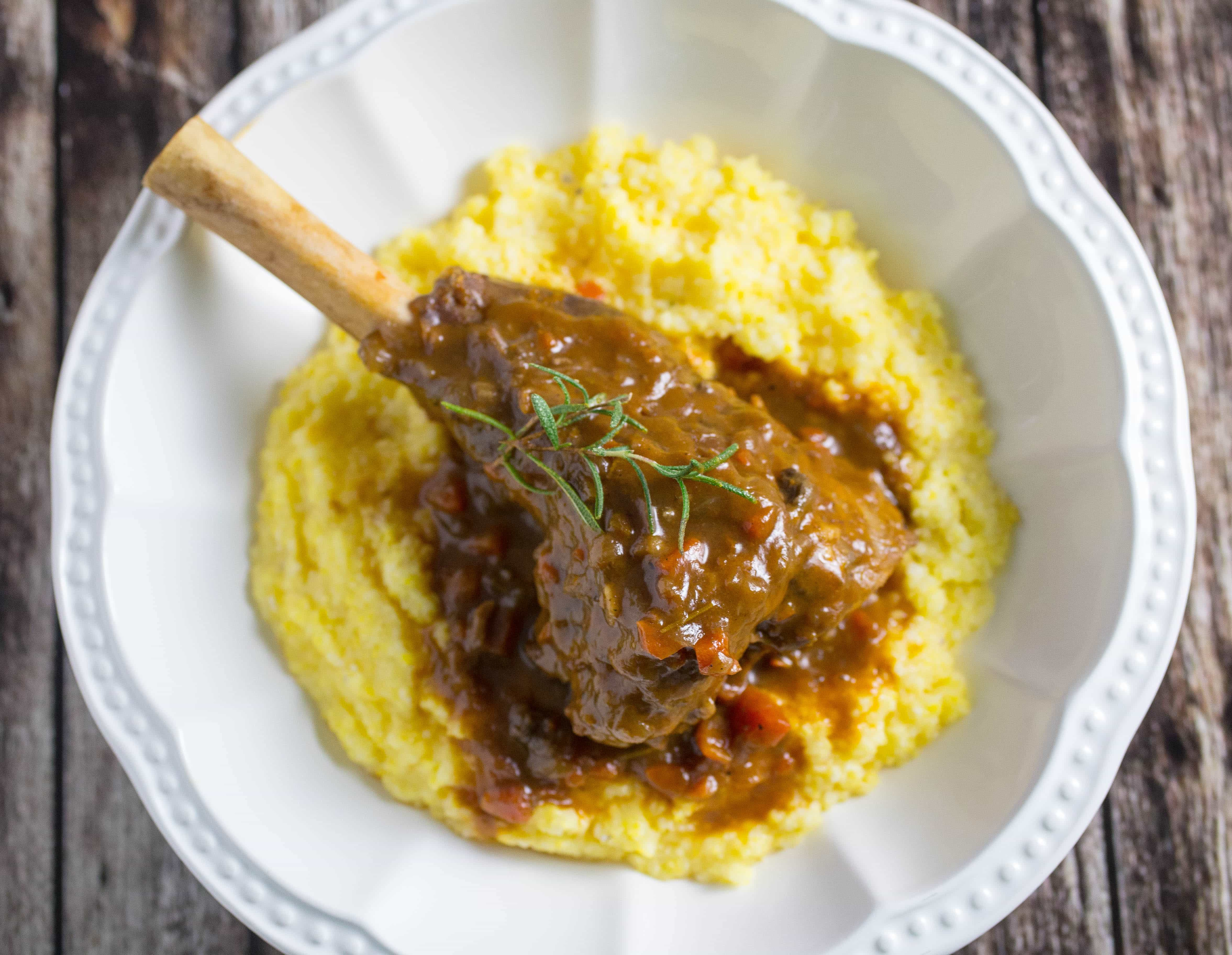 Overhead shot of a Lamb Shank in a white bowl on a wooden table