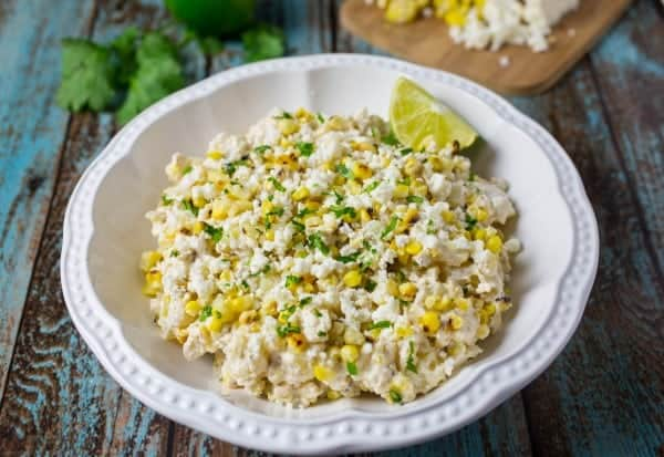 Mexican Street Corn Potato Salad in a white bowl with fresh cilantro in the background.