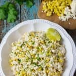 A bowl of Mexican street corn potato salad with fresh cilantro in the backgroudn with charred corn and cheese on a wooden cutting board.