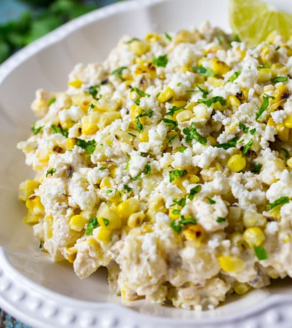 Close up photo of corn potato salad in a bowl with chopped herbs on top.