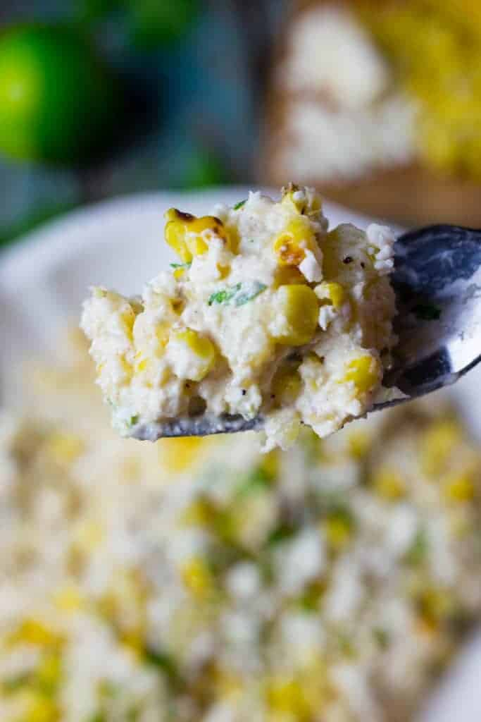 Close up of creamy Mexican street corn potato salad on a fork.