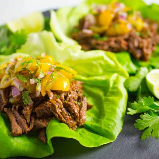 Shredded beef tacos in lettuce leaves on plate
