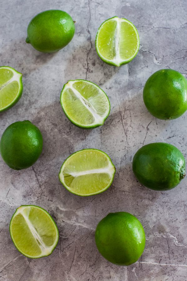 Whole limes and cut limes on a marble board.