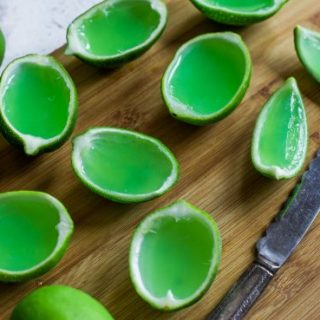 Cut slices of Margarita Jello Shots made in lime cups and on a cutting board