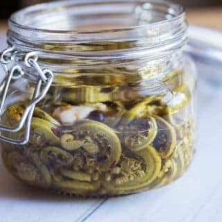 Spicy Pickled Fiddleheads in a glass jar with a lid