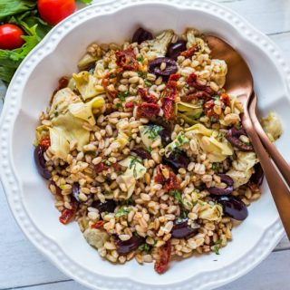 Mediterranean Farro Salad in a white bowl with a serving spoon