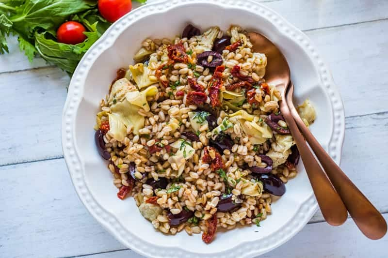 Farro grained salad in a serving bowl with a spoon