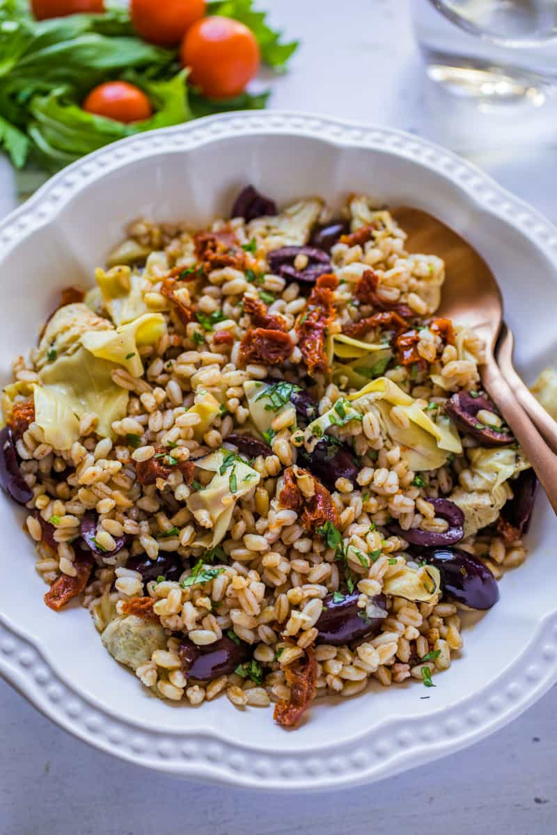 Mediterranean Farro Salad in a large white bowl with a serving spoon