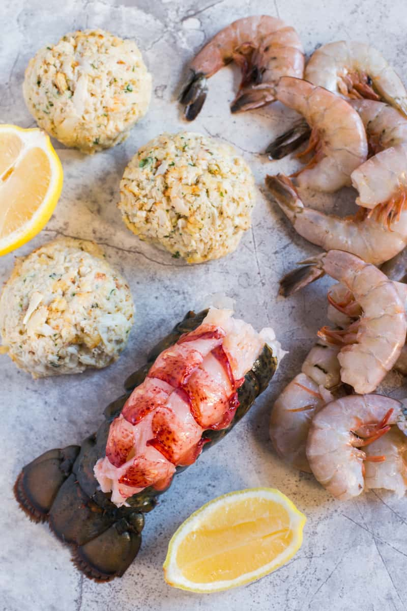 Display of uncoooked crab cakes, shrimp, and lobster tail for the Seafood Appetizer Platter with Homemade Mustard Sauce recipe