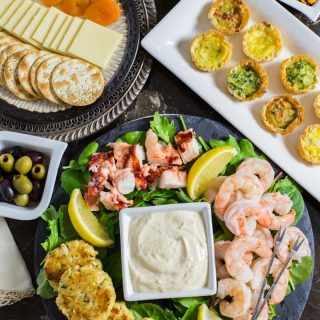 A variety of appetizers on a table (cut cheese and crackers, cooked seafood, and mini quiches)