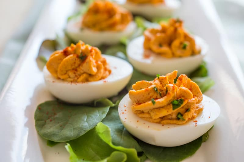 Close up of Best Deviled Eggs on plate with lettuce