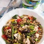 Bowl of Grilled Vegetable Tuna Salad on table with cans of tuna