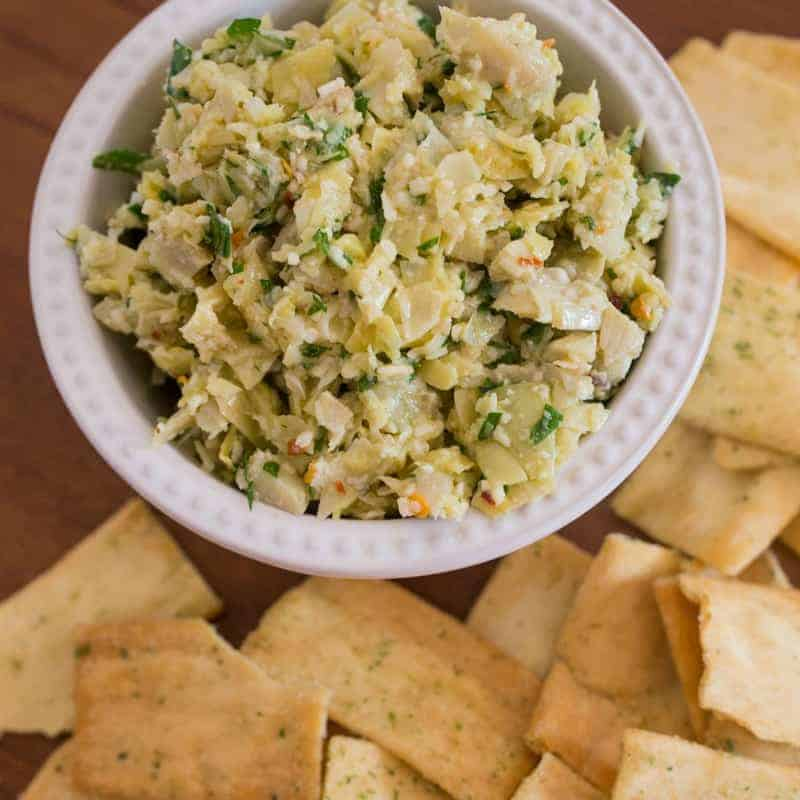 Artichoke dip recipe in a bowl with chips around it