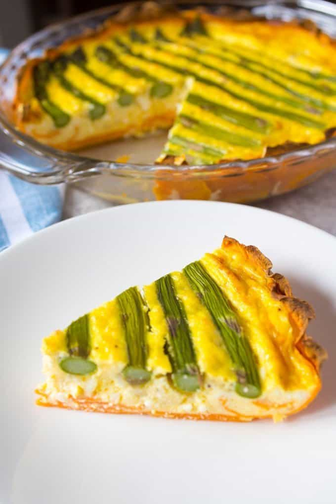 A slice of low carb quiche with asparagus and a sweet potato crust on a plate